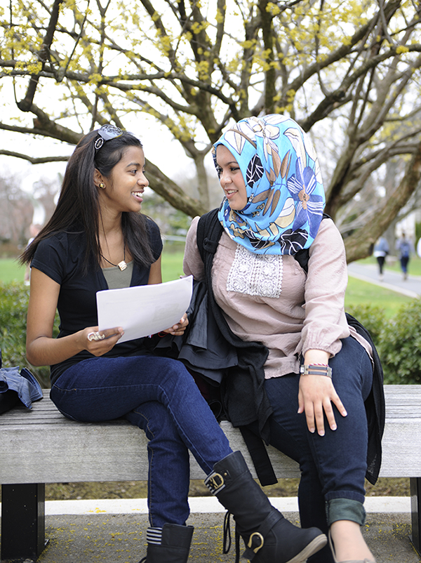 Two female students sit on a bench at Adelphi and talk